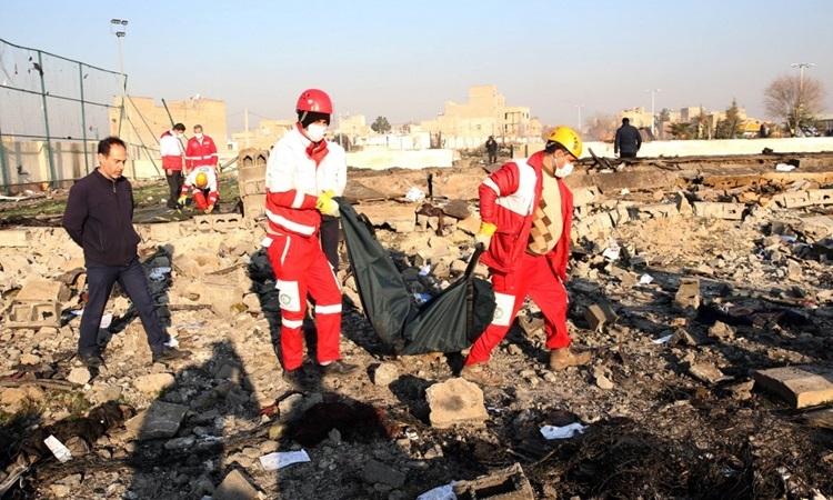 Nhân viên cứu hộ di chuyển thi thể một nạn nhân tại hiện trường rơi máy bay ở ngoại ô Tehran, Iran hôm nay. Ảnh: AFP.