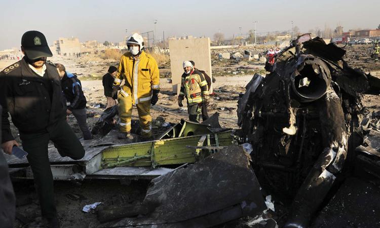 Lực lượng cứu hộ làm việc cạnh mảnh vỡ máy bay cháy sém sau tai nạn ở Tehran hôm 8/1. Ảnh: AP.