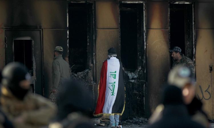 Người biểu tình quàng quốc kỳ Iraq đứng trước đại sứ quán Mỹ tại Baghdad hôm 1/1. Ảnh: AFP.