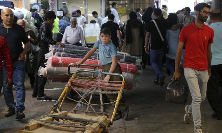Cậu bé đứngbên xe đẩy hàng tại chợ ở thủ đô Tehran, Iran hồi tháng 7/2019. Ảnh: AP.
