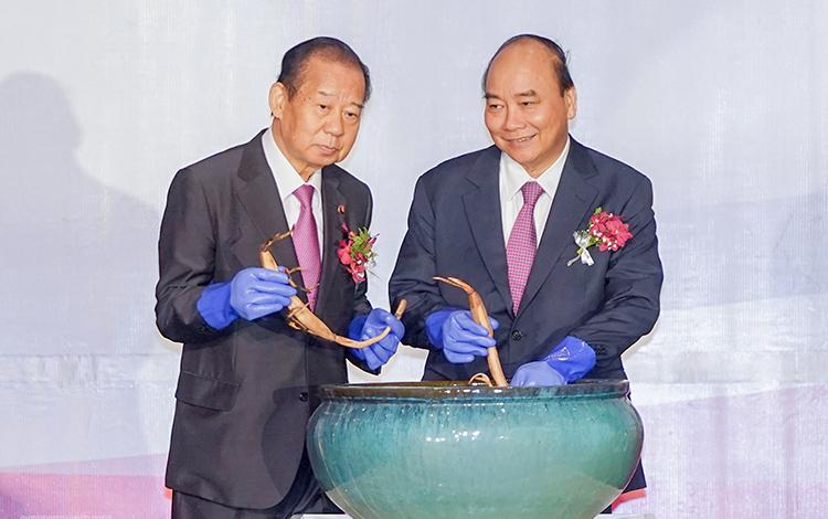 Thủ tướng Nguyễn Xuân Phúc và Tổng Thư ký Nikai thực hiện nghi thức trồng sen Oga. Ảnh: VGP/Quang Hiếu.