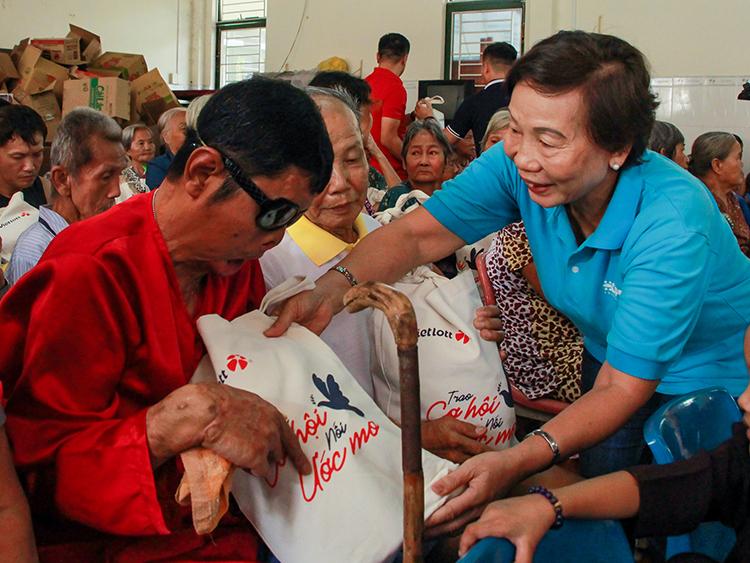 Đại diện Quỹ Hy vọng trao quà cho ông Liêm (áo đỏ, phải) tại Mái ấm Mây Ngàn chiều 10/1. Ảnh:Thanh Trần