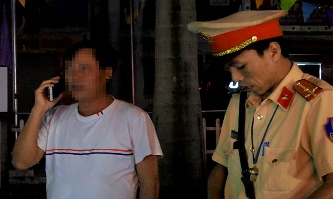 Tài xế Hạn (áo trắng) gọi điện nhờ người thân can thiệp khi bị cảnh sát đo độ cồn. Ảnh: Hùng Lê