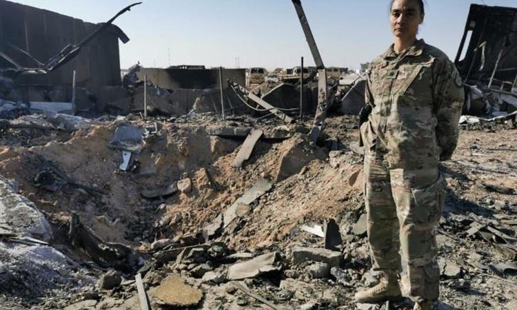Trung tá Staci Colemsan đứng cạnh hố sâu lớn do tên lửa Iran gây ra tại căn cứ Al-Asad hôm 11/1. Ảnh: CNN.