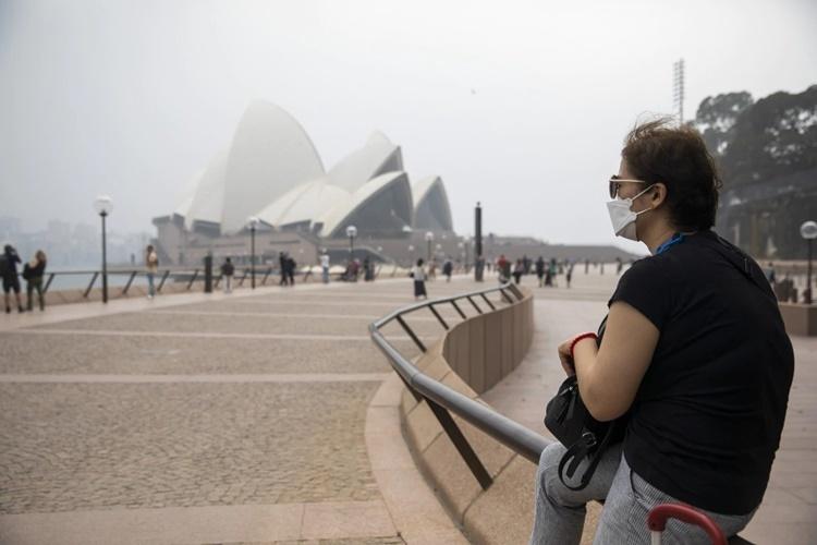 Một phụ nữ đeo khẩu trang ngồi gần Nhà hát Opera Sydney ngày 8/1. Ảnh: Bloomberg News.