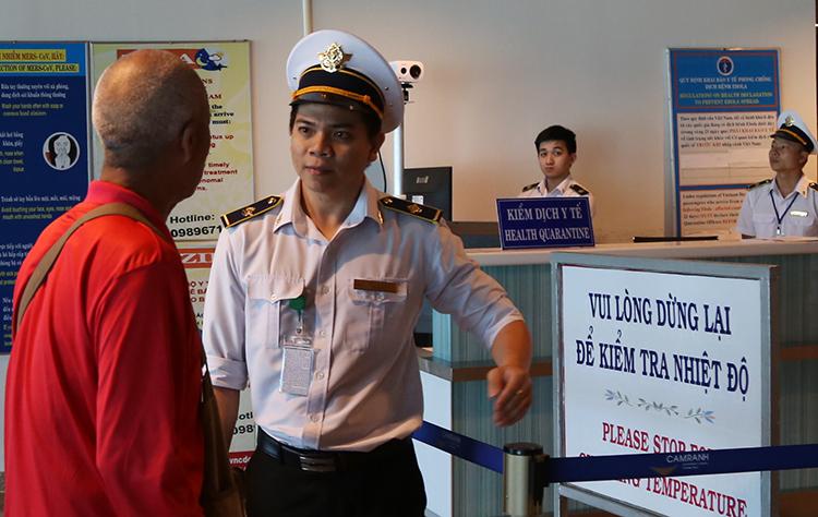 Anh Hoàng Đức Tú mời khách Trung Quốc kiểm tra y tế trước khi nhập cảnh vào Khánh Hòa, chiều 13/1. Ảnh: Xuân Ngọc.
