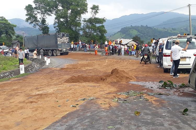 Nhà chức trách đổ đất ra mặt đường để làm sạch dầu tràn.Ảnh:Quang Hà