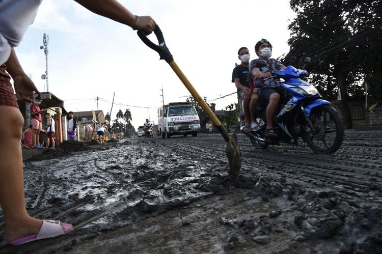 Người dân ở phía nam Manila cào bùn  từ núi lửađọng lại sau mưa ngày 13/1. Ảnh: AFP.