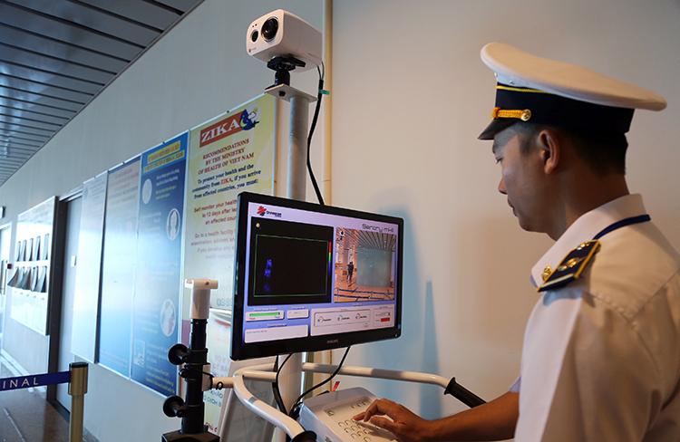 Nhân viên của Trung tâm Kiểm dịch y tế quốc tế theo dõi thân nhiệt khách Trung Quốc, qua