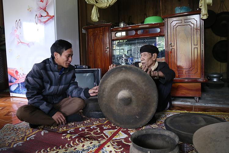 Già Kôn Pruôi giới thiệu chiêng cổ với một thanh niên ở trong xã. Ảnh: Hoàng Táo