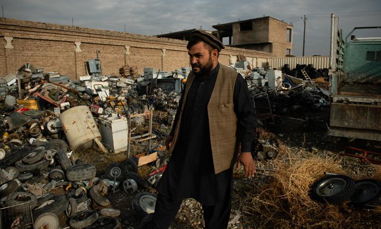 Sayeed Jamal Nasari đứng ở xưởng phế liệu của anh ở Bagram. Ảnh: NY Times.