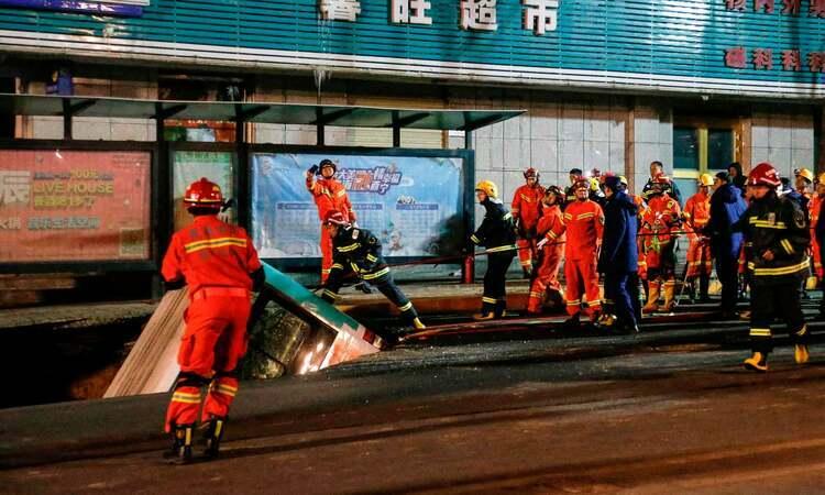 Lực lượng cứu hộ chuẩn bị kéo xe buýt ra khỏi hố sụt ở thành phố Tây Ninh, tỉnh Thanh Hải, Trung Quốc hôm 13/1. Ảnh: AFP.