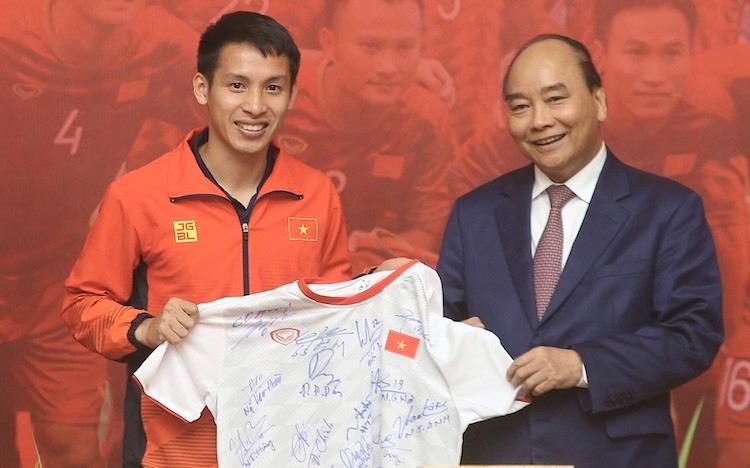 Thủ tướng được đội tuyển bóng đá nam tặng áo có chữ ký tại buổi gặp mặt tháng 12/2019. Ảnh: Gia Chính