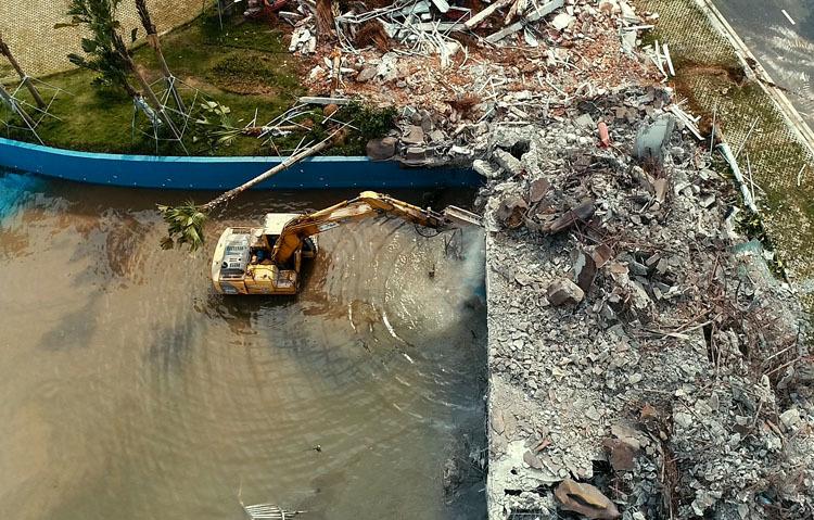 Máy xúc phá dỡ khu vực bể bơi của Công viên nước Thanh Hà. Ảnh: Tất Định