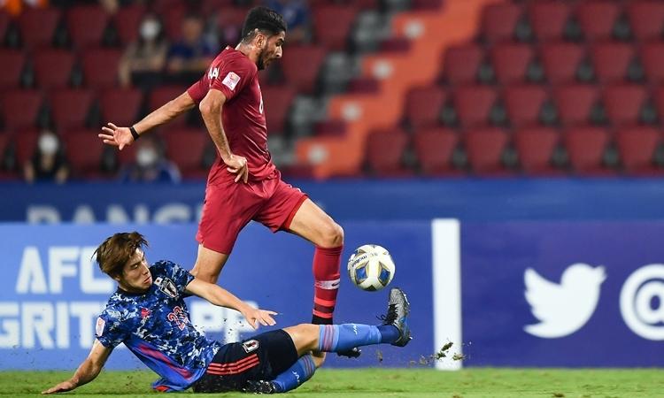 Nhật Bản (áo xanh) lấn lướt Qatar, ngay cả khi chơi thiếu người. Ảnh: AFC.