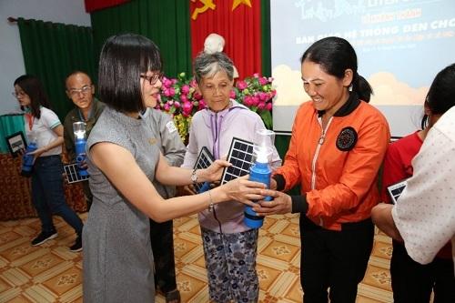 Bà Nguyễn Thị Hương - Phó tổng giám đốc ABBank (trái) đại diện nhà tài trợ trao tặng đèn năng lượng mặt trời cầm tay cho bà con.
