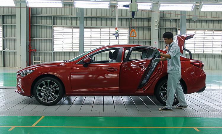 Công nhân hoàn thiện xe trong nhà máy của Mazda. Ảnh: Đức Huy