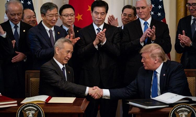 Phó thủ tướng Trung Quốc Lưu Hạc (ngồi bên trái) và Tổng thống Mỹ Donald Trump (ngồi bên phải) ký thỏa thuận thương mại giai đoạn một ngày 15/1 tại Nhà Trắng. Ảnh: New York Times.
