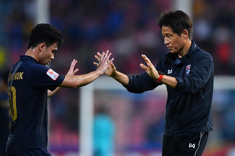 HLV Nishino (phải) ăn mừng cùng cầu thủ Thái Lan sau khi vượt qua vòng bảng. Ảnh: AFC.