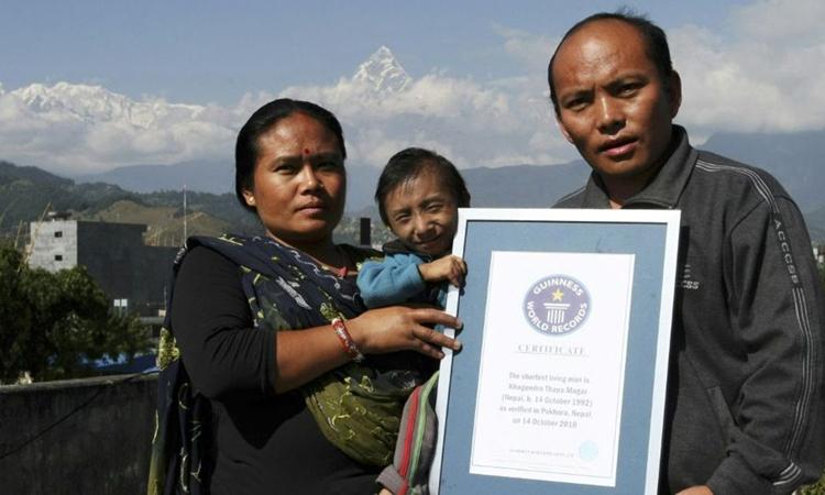 Magar (giữa) chụp ảnh với chứng nhận Guinness cùng bố Roop Bahadur và mẹ Dhan Maya ở Pokhara, tháng 10/2010. Ảnh: AFP.
