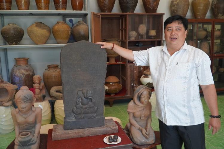 Nhà sưu tâm Nguyễn Ngọc Ẩn bên tấm bia đá cổ thời tiền Angkor. Ảnh: Việt Quốc