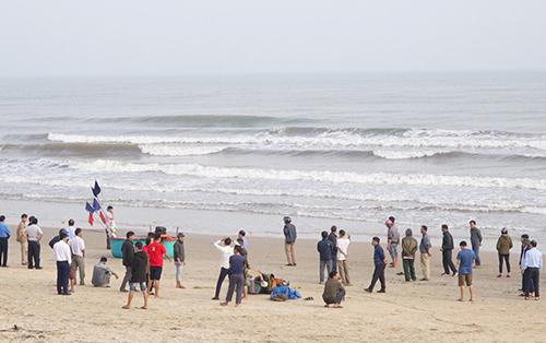 Nhiều người tập trung trên bờ biển Thiên Cầm theo dõi nhà chức trách tìm kiếm thi thể. Ảnh: Đ.H