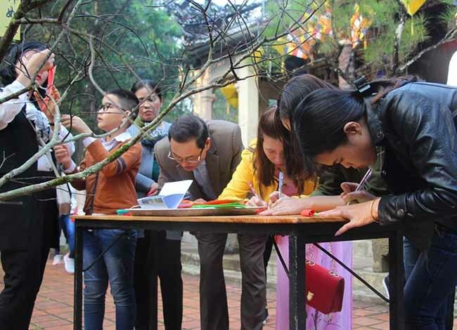 Người dân lên chùa ghi nguyện ước treo lên cây nguyện ước trước chánh điện chùa. Ảnh: Võ Thạnh