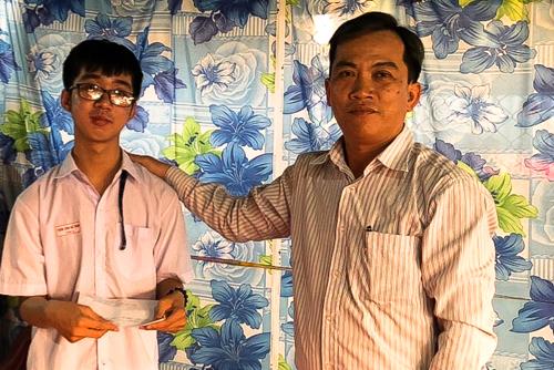 Thầy hiệu trưởng Lê Văn Dũng đến thăm, tặng quà một học sinh có hoàn cảnh đặc biệt của trường. Ảnh: Cửu Long