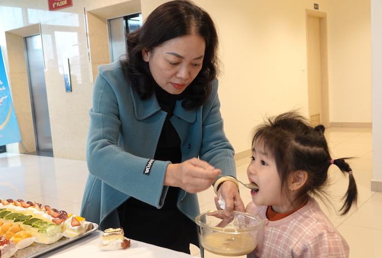 Bà Lê Thị Xá tranh thủ cho cháu nội ăn trước khi dự chương trình giao lưu, trò chuyện online với con trai và con dâu ngày 20/1. Ảnh: HT