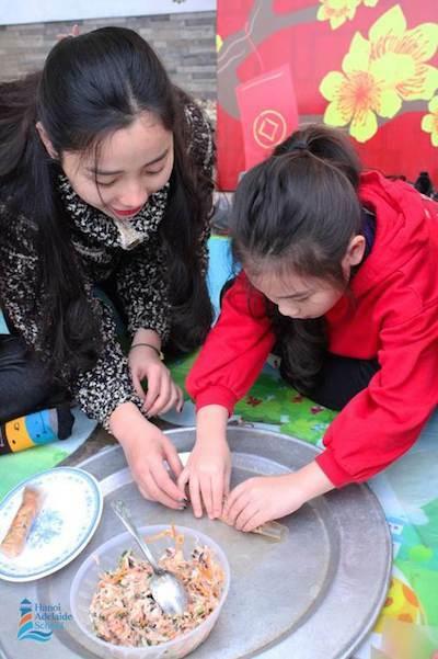 Học sinh đang được cô giáo hướng dẫn gói nem, món ăn truyền thống trong mâm cỗ tết