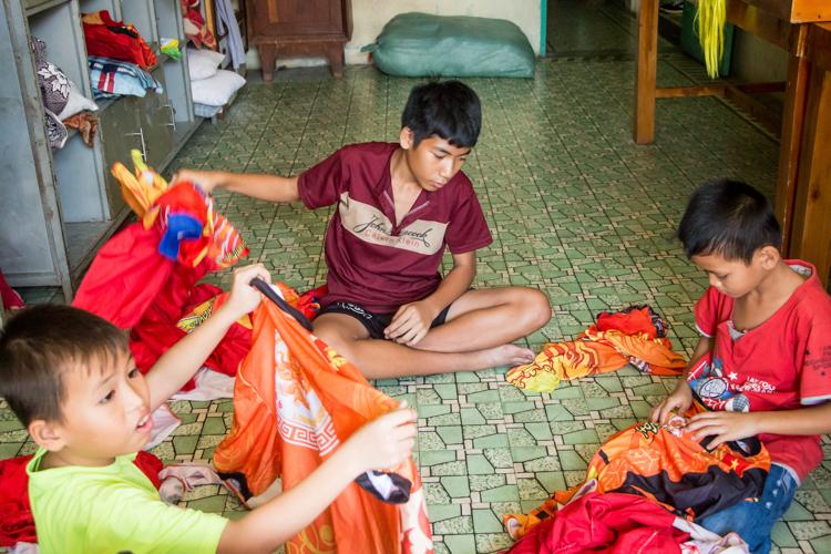 Các thành viên của đội Long Nhi Đường chuẩn bị trang phục diễn dịp Tết tại nhà. Ảnh: Thanh Trần