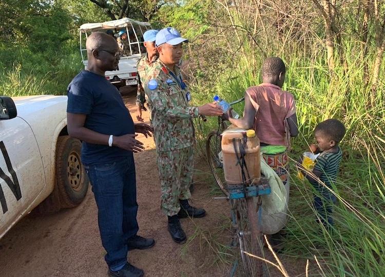 Trung tá Lương Trường Vinh đưa nước và đồ ăn để trấn tĩnh hai đứa trẻ lao xe vào bụi rậm lẩn trốn khi nhầm đoàn xe Liên Hợp Quốc là xe quân sự của nhóm vũ trang. Ảnh: Cục GGHB