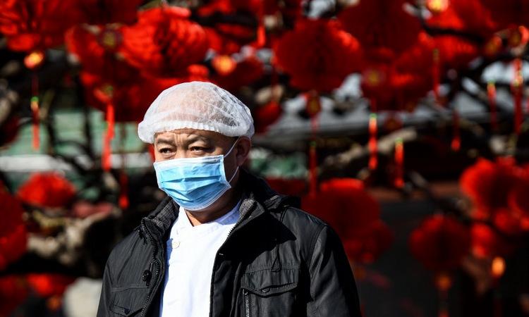 Một người dân trên đường phố Bắc Kinh chiều 23/1. Ảnh: AFP.