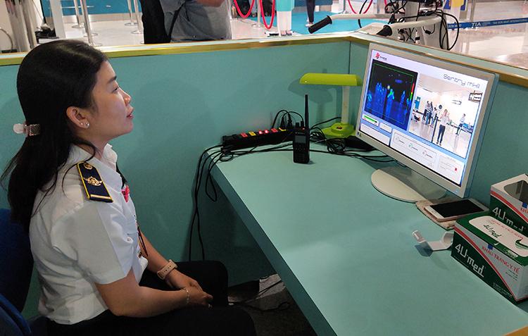 Kiểm tra thân nhiệt hành khách nhập cảnh qua sân bay Tân Sơn Nhất. Ảnh: Hữu Nguyên