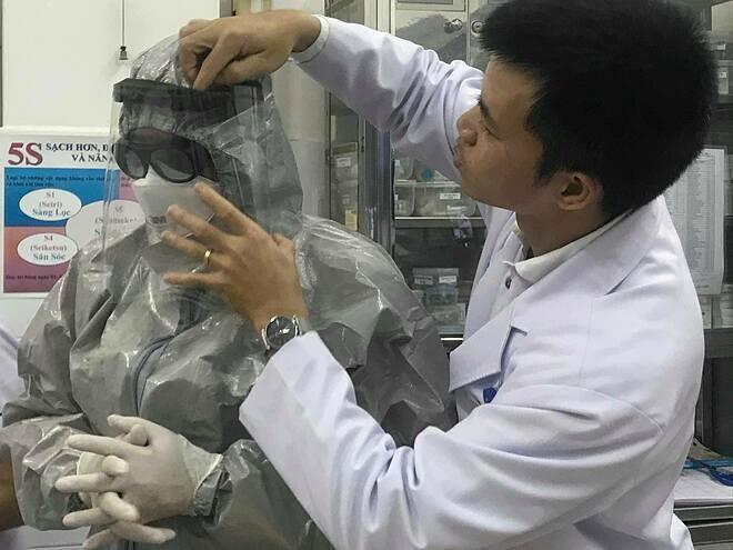 Thứ trưởng Y tế Nguyễn Trường Sơn mặc đồ bảo hộ vào thăm 2 bệnh nhân đang điều trị tại Bệnh viện Chợ Rẫy tối 23/1. Ảnh: Đ.H.