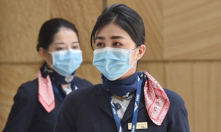Tiếp viên trên chuyến bay từ Vũ Hán đến Sydney hôm 23/1. Ảnh: AFP.