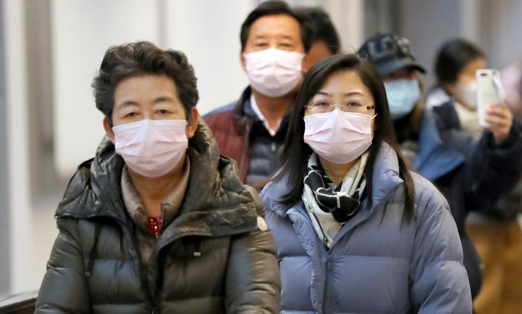 Hành khách trên chuyên bay cuối cùng từ Vũ Hán tới Tokyo hôm 23/1. Ảnh: Reuters.