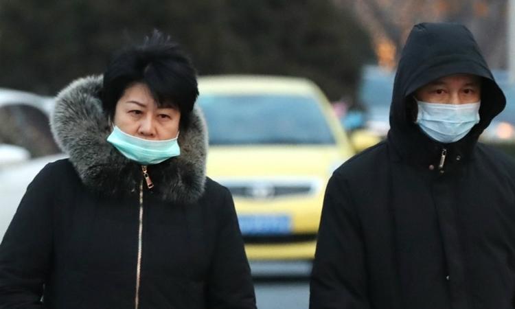 Hai người đi trên đường tại Vũ Hán, Trung Quốc ngày 22/1. Ảnh: Reuters.