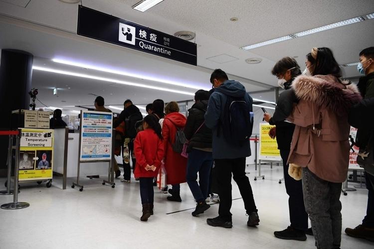Hành khách từ Vũ Hán đi qua cổng kiểm tra y tế tại sân bay ở Tokyo ngày 23/1. Ảnh: AFP.