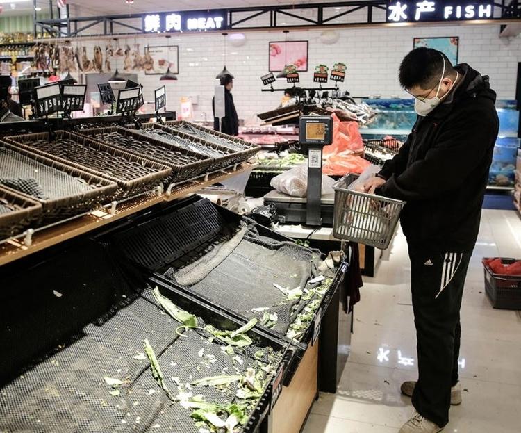 Một người đi siêu thị ở Vũ Hán ngày 23/1. Ảnh: Business Insider.