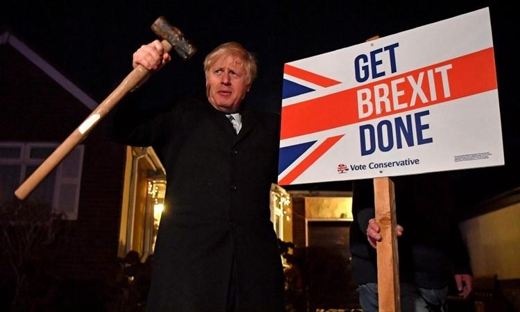 Thủ tướng Anh Boris Johnson giương búa cạnh biển Hoàn tất Brexit tại London tháng 12/2019. Ảnh: AFP.