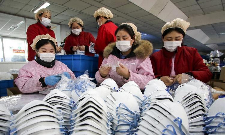 Công nhân làm việc tại một nhà máy khẩu trang ở tỉnh Hồ Bắc hôm 22/1. Ảnh: China Daily.