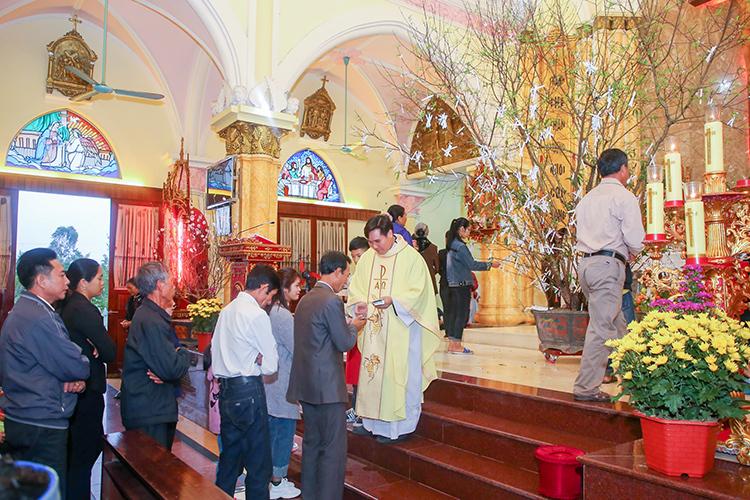 Tại giáo xứ Phúc Lạc (Giáo phận Thanh Hoá) giáo dân được nhận lì xì từ linh mục và lên cung thánh hái lộc treo trên cây đào. Ảnh: Nguyễn Dương.