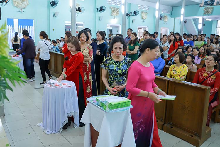 Các tín hữu xếp hàng trật tự lên nhận lộc thánh và thiệp chúc mừng năm mới. Ảnh: Nguyễn Đông.