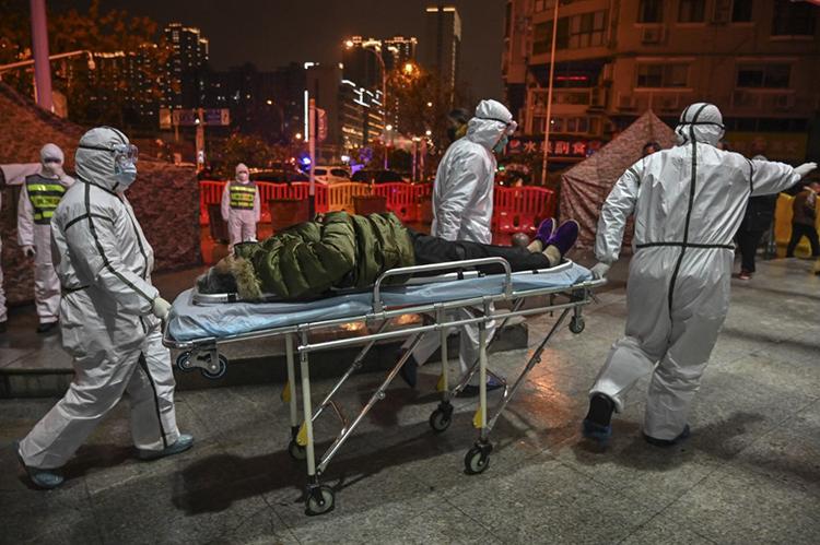 Các nhân viên y tế mặc đồ bảo hộ chuyển một người bệnh nghi nhiễm virus nCoV đến bệnh viện Chữ Thập đỏ Vũ Hán hôm qua. Ảnh: AFP