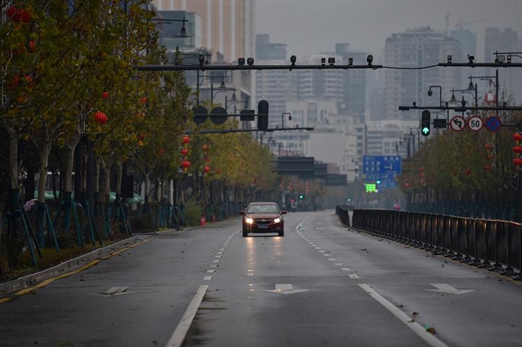 Một xe hơi đơn độc trên đường phố Vũ Hán hôm nay. Ảnh: AFP