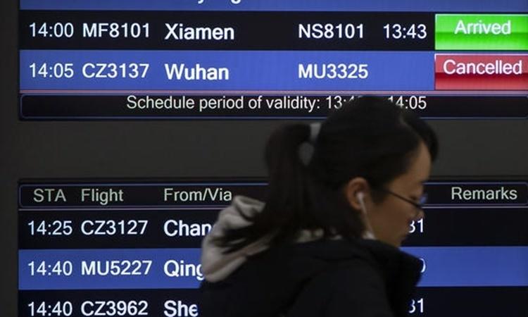 Một hành khách đi qua tấm bảng thông báo tình trạng chuyến bay tại sân bay Bắc Kinh ngày 23/1. Ảnh: AP.