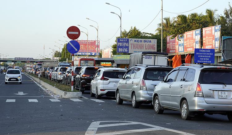 Dù trạm thu phí xả cửa,ôtô vẫn phải xếp hàng chờ qua cầu Rạch Miễu. Ảnh: Hoàng Nam.