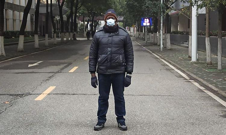 Khamis Hassan Bakari đứng trên phố vắng người vì dịch viêm phổi ở Vũ Hán. Ảnh: AP.