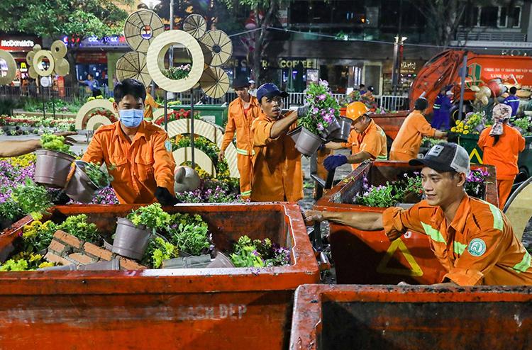 Công nhân vệ sinh thu dọn đường hoa Nguyễn Huệ đêm Mùng 4 Tết. Ảnh: Quỳnh Trần